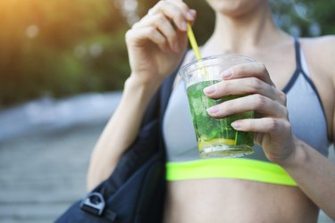 Woman drinking herbal tisane after fitness running workout on summer day