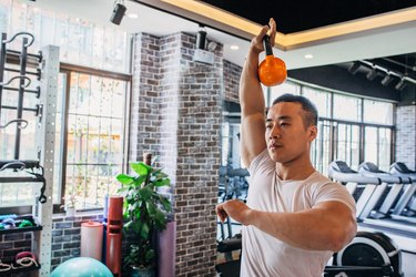 Muscular man is working out with kettlebell