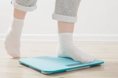 female legs on electronic scales on  wooden floor