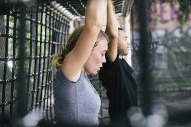 Young Woman Exercising With Colleague Outdoors