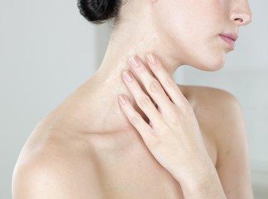 Young woman moisturizing neck
