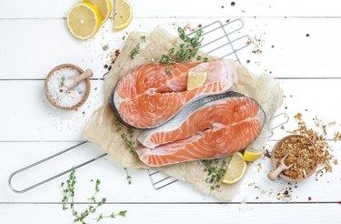 Raw salmon steak on white wooden background top view