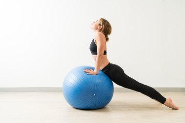 Side View Of Young Woman Stretching During Workout