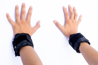 Pair of hands isolated on white of a male wearing black colored wrist weights in his hands.
