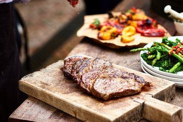Freshly cooked steak on wooden board with salt flakes