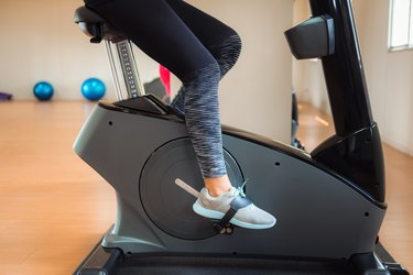 Low Section Of Woman Cycling On Exercise Bike In Gym