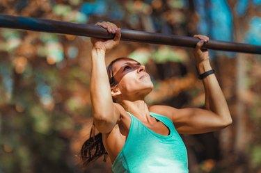 Female Athlete Exercising On Gymnastics Bar In Park
