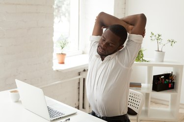 Man doing chair yoga poses by stretching arms overhead at his desk