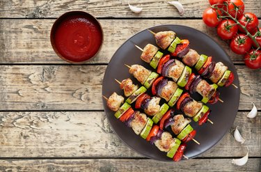 Chicken or turkey meat kebab skewers with ketchup, tomatoes