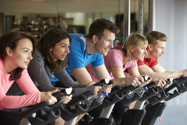 Side view of a spinning class on exercise bikes at
