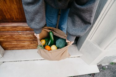 Young woman is picking up a bag of vegetables and fruit just delivered to her home