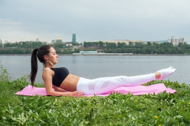 Fit woman working out on her strength of stomach  abs. Leg lift sit-up.