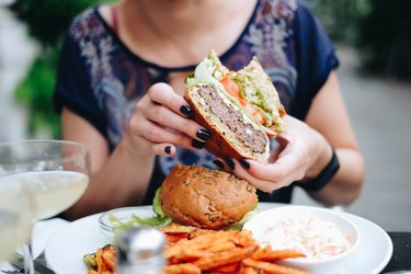 Midsection Of Woman Holding a Burger At Restaurant