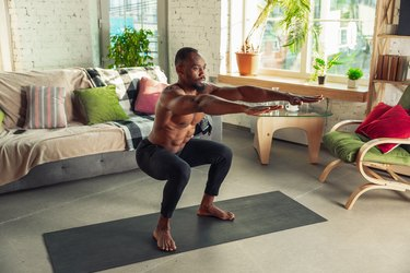 Young african-american man teaching at home online courses of fitness, aerobic, sporty lifestyle while being quarantine