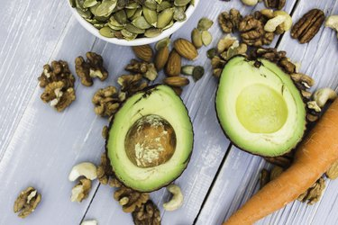 Healthy food and dieting concept. Focus on avocado. Carrots, nuts: cashews, almonds, pecans, walnuts, pumpkin seeds on a wooden table. Light summer flat lay food