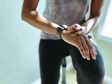 Woman Checks Her Fitness Stats on Smart Watch after Indoor Cycling Workout