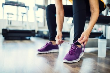 lower section of woman tying purple sneaker in a gym