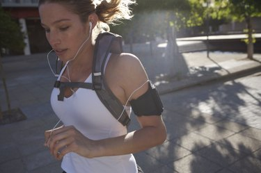Woman jogging outdoors with backpack and earphones, close-up