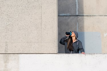 woman drinking protein shake with muscle milk after workout