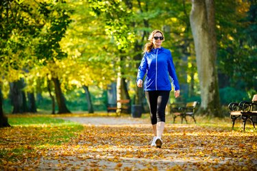 A middle-aged woman walking in the park for exercise