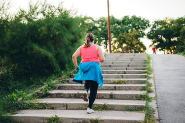 woman in pink tank top running up stairs outside