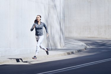 Female jogger with headphones on street