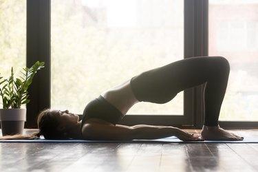 Woman doing pilates or yoga Glute Bridge pose