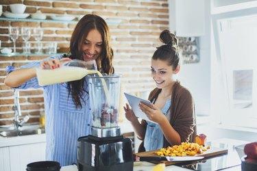 Caucasian women making smoothie in kitchen