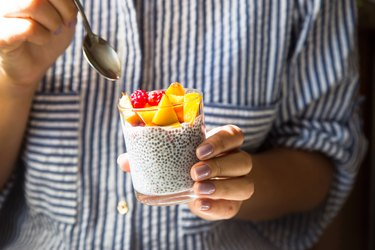 Chia pudding on coconut milk with raspberries and peach in a glass jar in female hands with a spoon. Raw vegan healthy food concept
