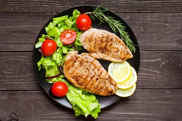 chicken grilled breast fillet with herbs, vegetables and lemon