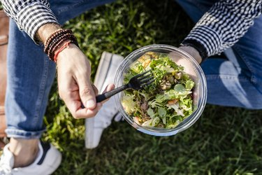 Man sitting on a meadow eating mixed salad, partial view