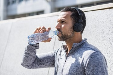 Man having a break from exercising wearing noise-cancelling headphones and drinking from bottle