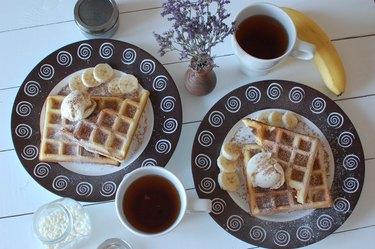 two white ceramic mugs beside plate of belgian waffles