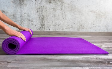 Low Section Of Person Rolling Yoga Mat