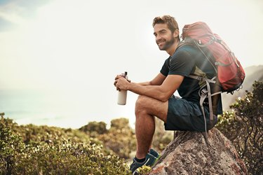Fit guy wearing a backpack and hiking in the wilderness