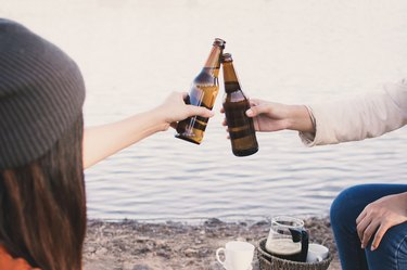 Friends Toasting Beer Bottles At Lakeshore