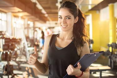 Personal trainer with clipboard showing thumb up in gym.