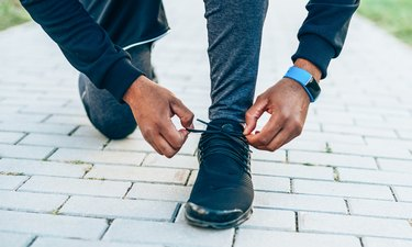 Man tying shoelaces preparing to run outside