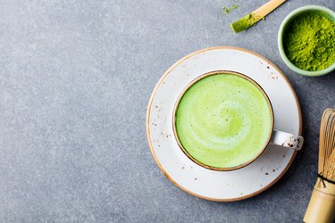 Matcha green tea latte in a cup. Top view. Copy space.