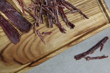 Close up shot of homemade shredded beef jerky on wooden cutting board
