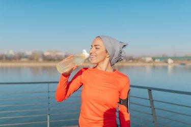 Beautiful young woman jogger drinking water