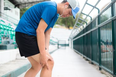 Man in blue shirt and cap with knee pain attempting a running workout