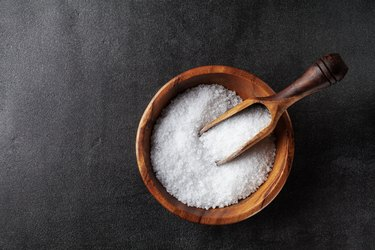 Salt in wooden bowl on black kitchen table top view.