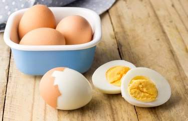 Hard boiled chicken eggs on rustic wooden table