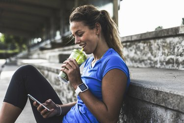 A young woman drinking a smoothie after a workout