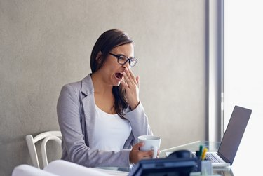 A woman yawning at her desk at work