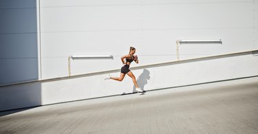 Young sportswoman running outdoors against wall