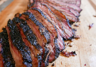 Sliced smoked brisket on a wooden cutting board.