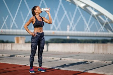 Young woman resting after jogging and drink on a sunny day