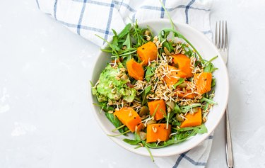 Green salad with sweet potatoes, guacamole and olives.